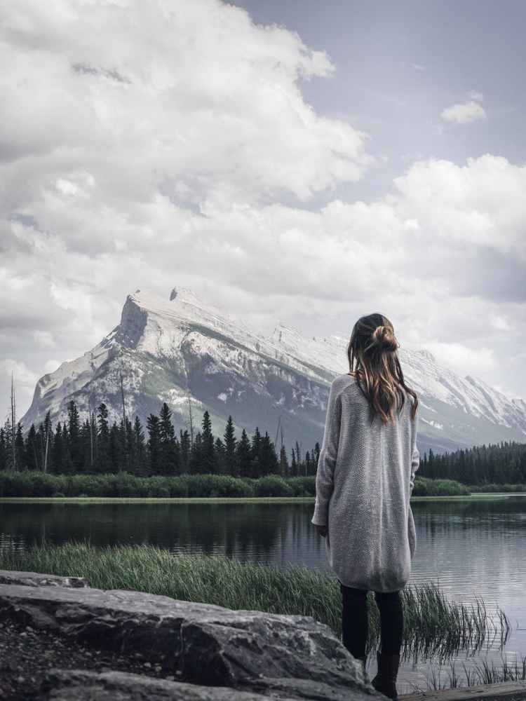 woman standing near rock in front of lake
