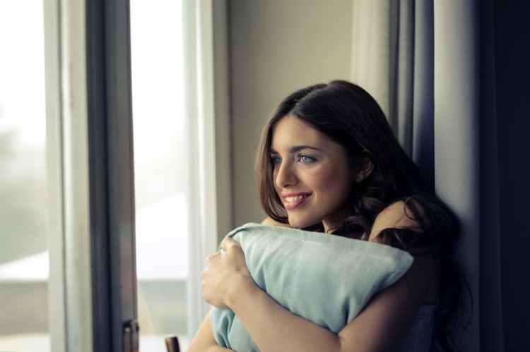 woman hugging white pillow beside glass door